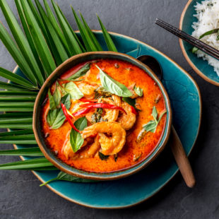 2020-02 - THAI SHRIMPS RED CURRY. Thailand Thai tradition red curry soup with shrimps prawns and coconut milk. Panaeng Curry in blue plate on gray background